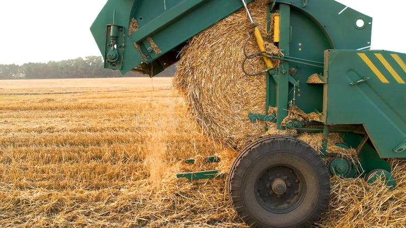 Machine making a round straw bale. Close up. Hay baling stock photo