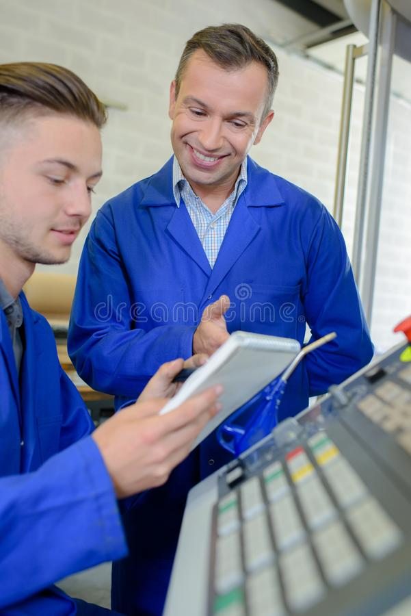 Machine operation with apprentice royalty free stock photos