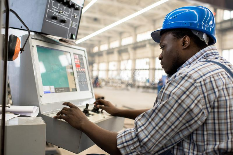 Machine Operator Focused on Work. Profile view of highly professional worker wearing protective helmet and overall operating machine at production department of stock photography