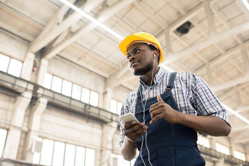 Machine Operator Listening to Music royalty free stock photo