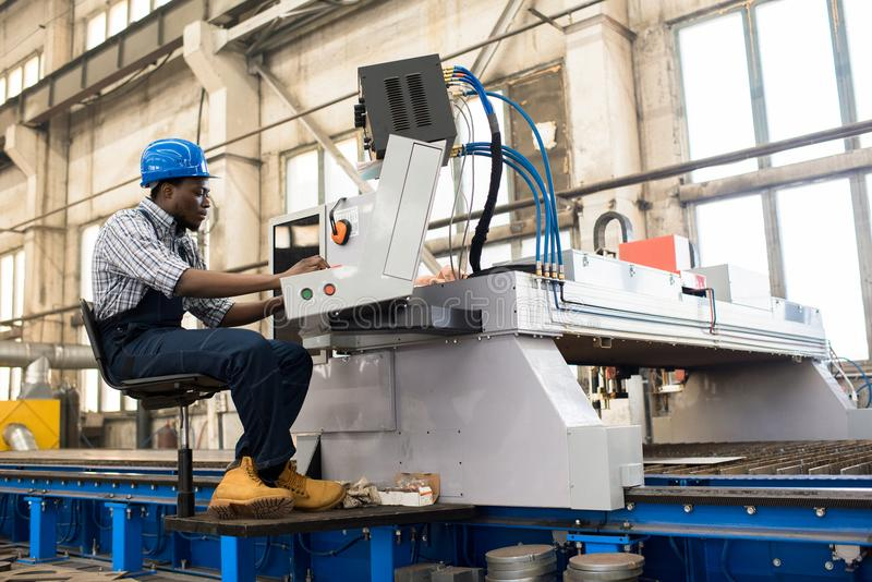 Machine Operator Wrapped up in Work. Profile view of young African American worker wearing overall and checked shirt operating machine unit at production royalty free stock images