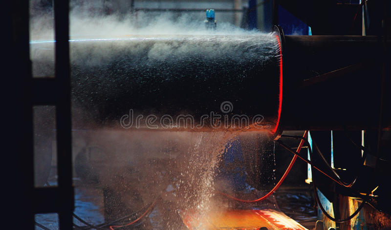 Machine oppression pipe. Burning hot pipe comes out of the machine that its oppression. Water cools it royalty free stock photo