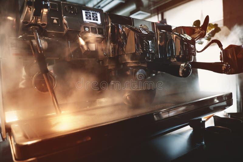 Machine professionnelle de café en vapeur tandis que barman faisant le café boire fouetter le lait dans le broc avec l'aide de photo libre de droits