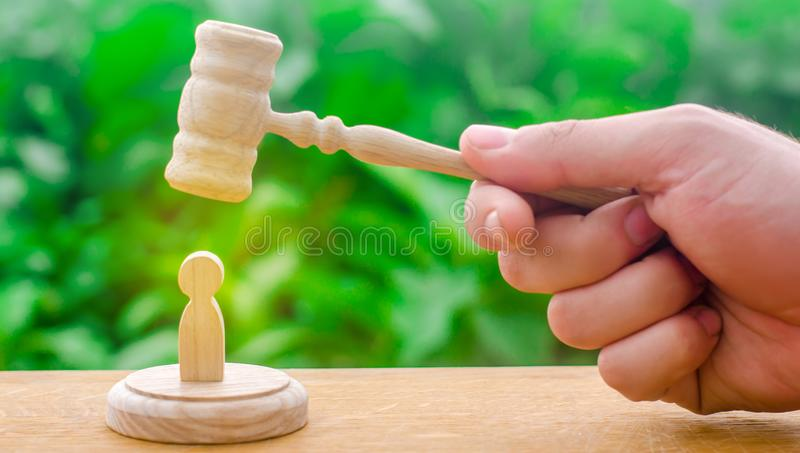 Machine repression and suppression of protests. The judge`s gavel hovered over the human figure. Concept of justice and litigatio stock image
