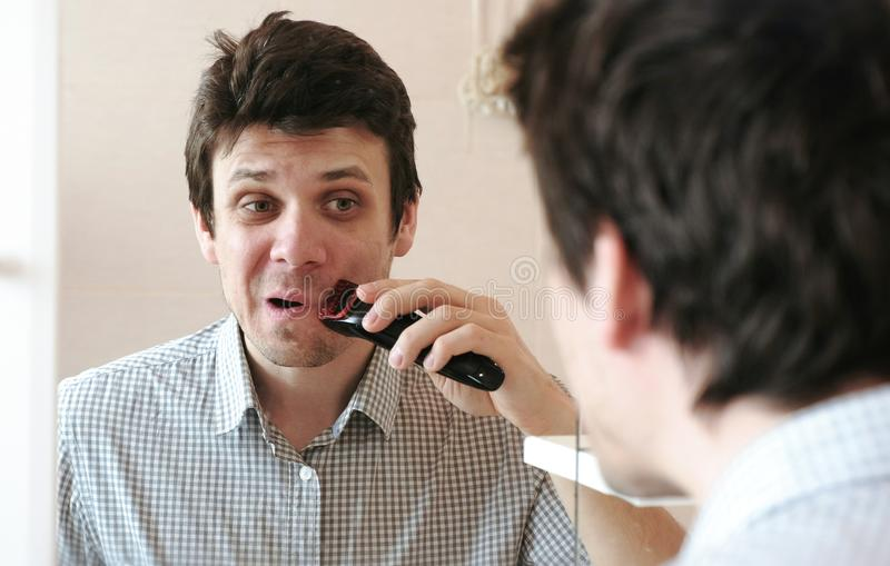 Machine shave facial hair. Young handsome man dry shaving with electric trimmer. stock image