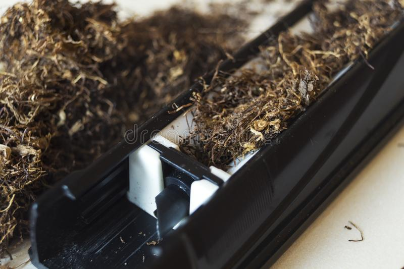 Machine for stuffing cigarettes with tobacco. Close up stock images