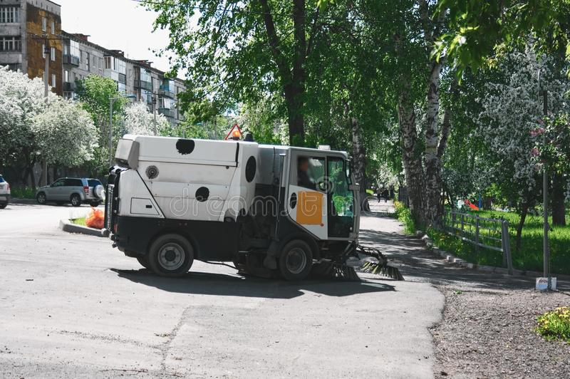 The special car cleans city road. Machine sweeper - cleaner cleans the roadway. Machine brushes sweeping the street. The car vacuumed on the street. Municipal stock images