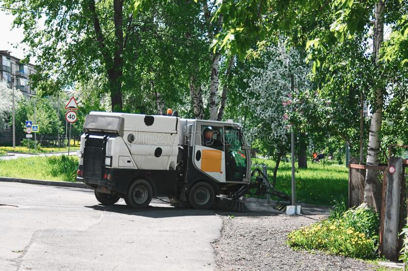 The special car cleans city road. Machine sweeper - cleaner cleans the roadway. Machine brushes sweeping the street. The car vacuumed on the street. Municipal royalty free stock photo