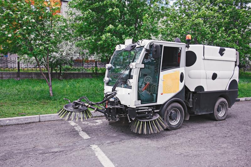 The special car cleans city road. Machine sweeper - cleaner cleans the roadway. Machine brushes sweeping the street. The car vacuumed on the street. Municipal stock photos