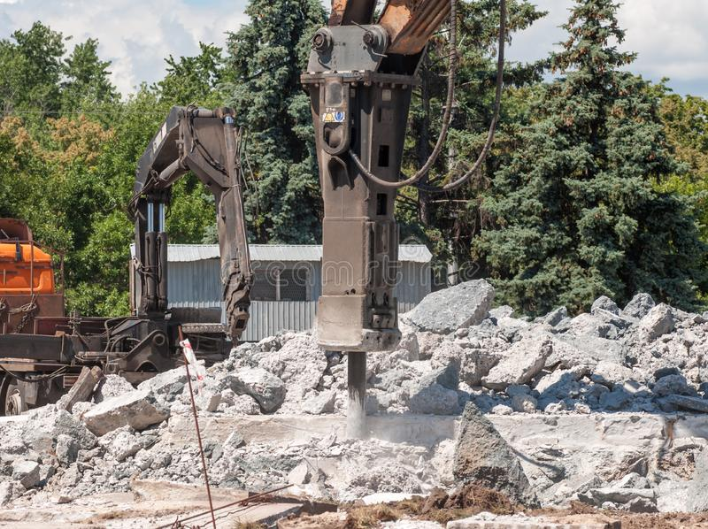 Machine to crush concrete. The crushing machine breaks the old concrete on the streets of the city royalty free stock image