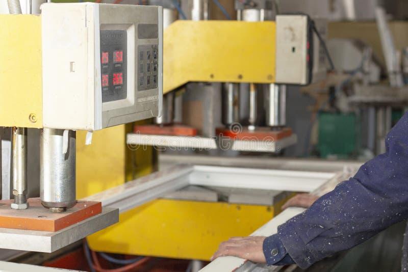Machineassemblage van plastic raamkozijnen bij de fabrieksvervaardiging van plastic vensters stock afbeeldingen