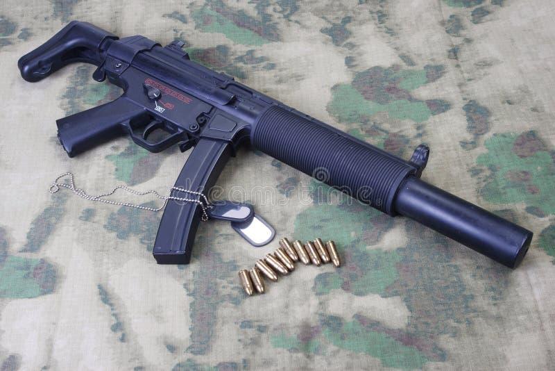 machinepistool MP5 met knalpot op gecamoufleerd stock foto's