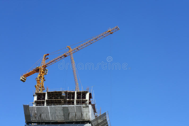 Machinery crane working in construction site building. Industry with blue sky background stock photo
