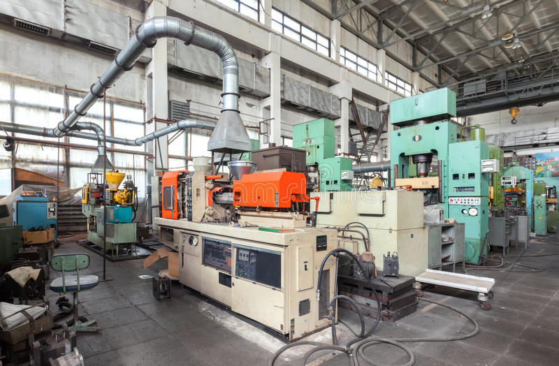 Machinery plant. Workshop for production of thermoplastic parts. Injection molding plastic machine and hydraulic press royalty free stock photo