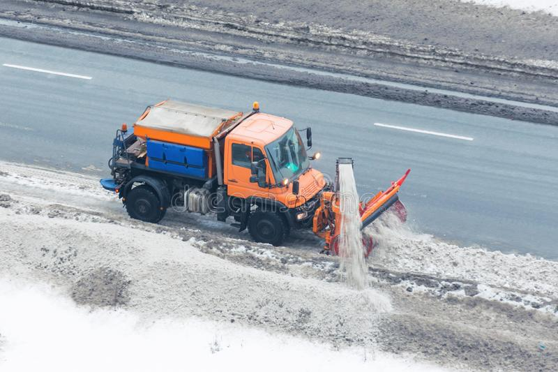 Machinery snowplough cleaning highway by removing cleans snow swinging on the side of the road stock photography