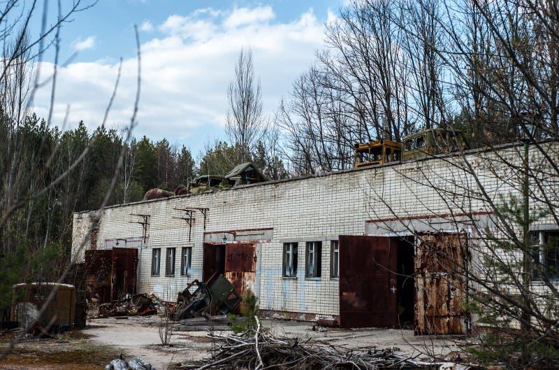 Machines cassées et abandonnées dans la zone d'exclusion de Chernobyl Bâtiment industriel avec les voitures cassées sur le toit image stock