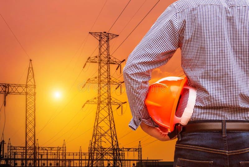 Machinez tenir le casque de sécurité jaune avec le pylône électrique à haute tension sur le coucher du soleil photos stock