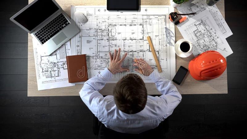Machinez vérifier nerveusement des dessins avant de commencer de la construction de bâtiments photos stock