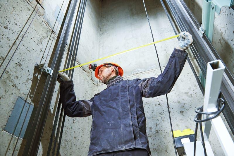 Machinist die met maatregelenband liftbouw in liftschacht controleren stock foto