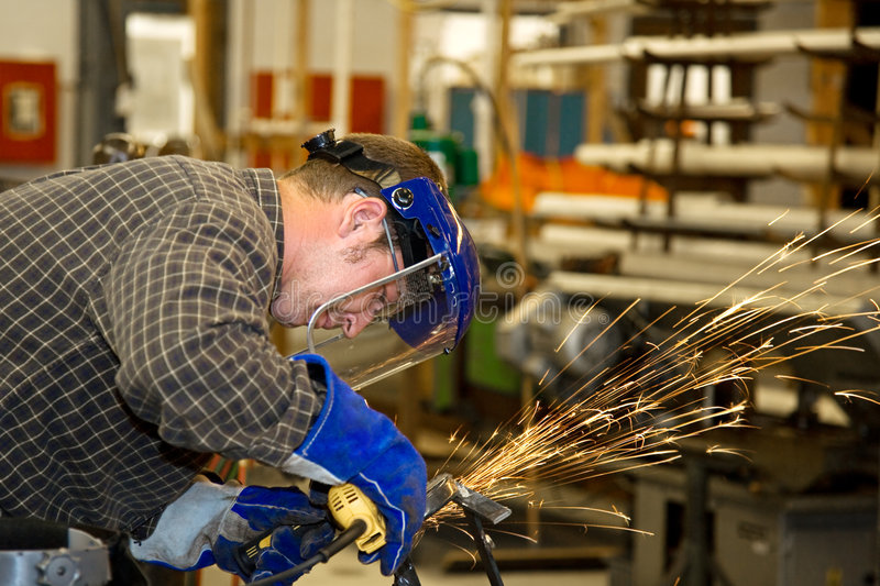 Machinist Grinding Metal. In a factory. Horizontal with room for text. Authentic and accurate content depiction in compliance with industry code and safety royalty free stock photos