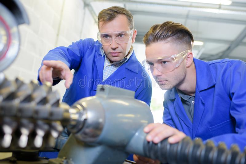 Machinist and apprentice royalty free stock image