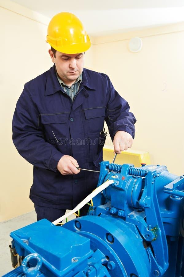 Machinist tuning elevator brakes mechanism royalty free stock photos