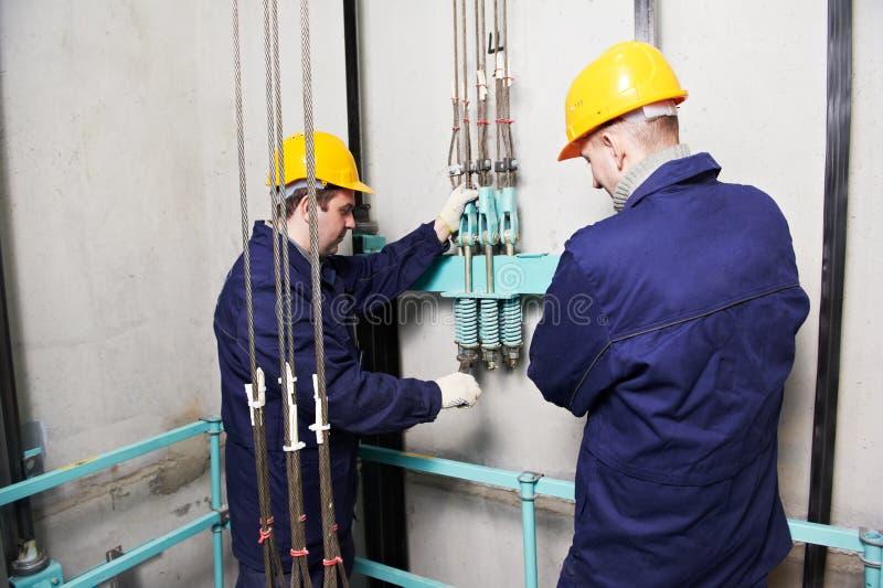 Machinisten die lift in hoistway lift aanpassen royalty-vrije stock afbeelding