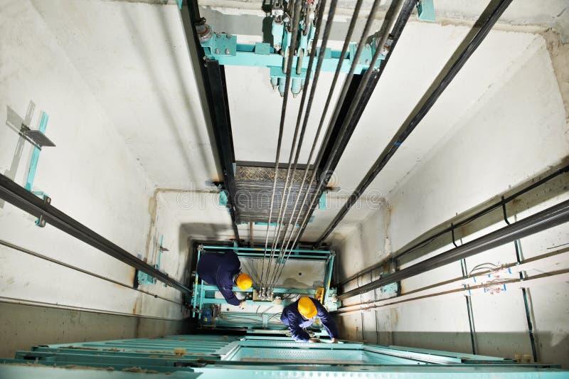 Machinisten die lift in hoistway lift aanpassen