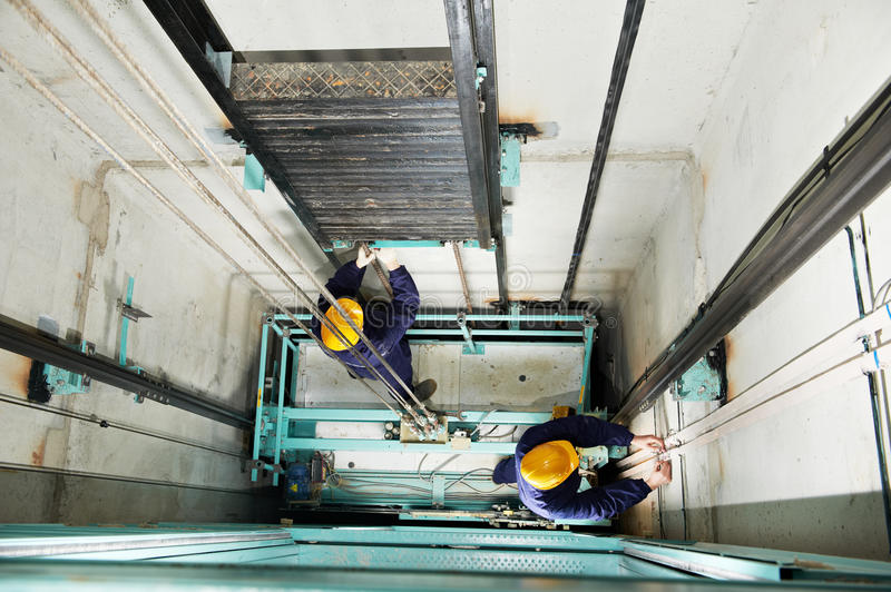 Machinists adjusting lift in elevator hoistway royalty free stock photos