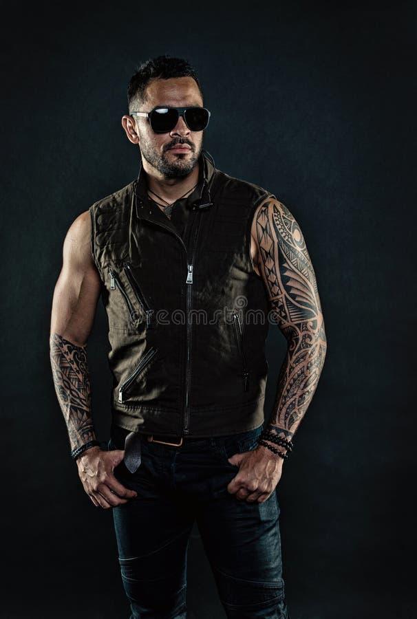Machista de la moda en gafas de sol de moda Modelo del tatuaje con la barba en cara sin afeitar El hombre barbudo con el tatuaje  fotografía de archivo