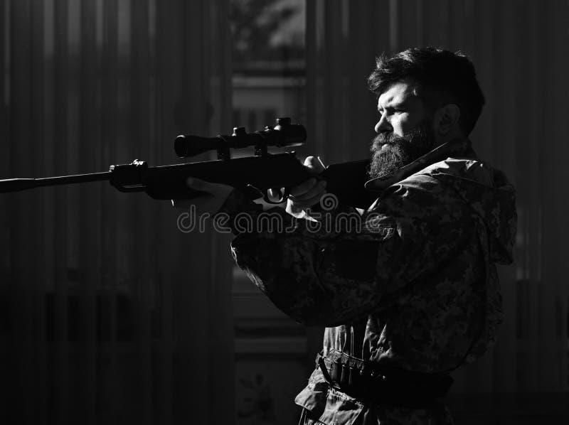 Machista en la cara sufridora de la mueca que tiene como objetivo a la víctima Cazador, soldado con el arma que apunta antes de t imagen de archivo libre de regalías