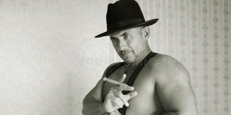 Machista muscular en un sombrero de fieltro fotografía de archivo libre de regalías