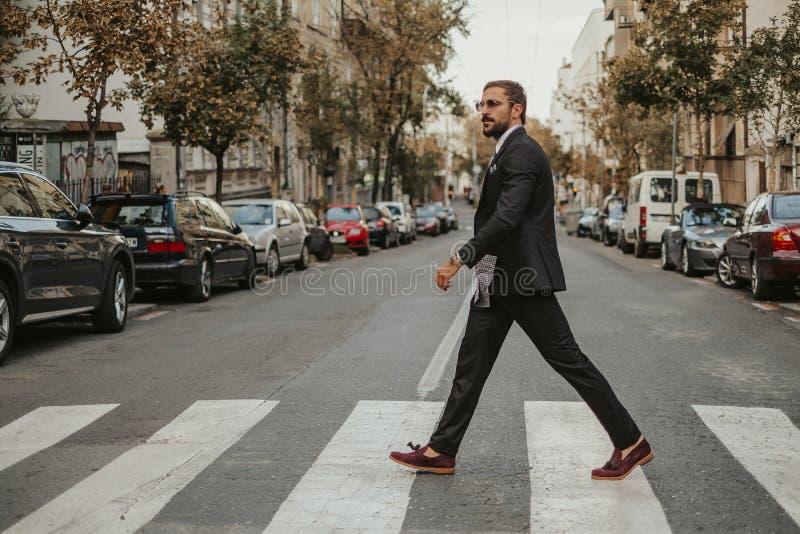 Macho affärsman som korsar gatan royaltyfria foton