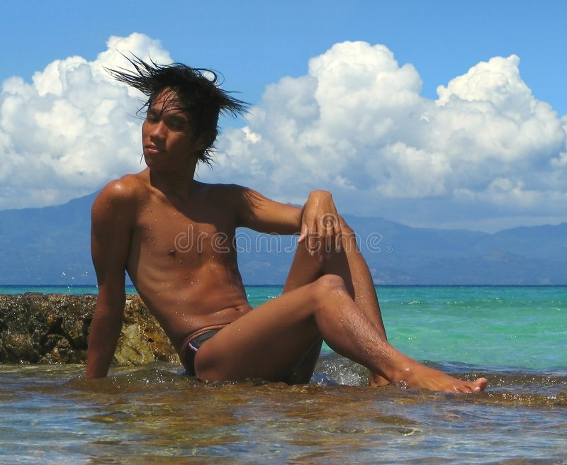 Macho asiático em rochas, swimwear. imagens de stock royalty free