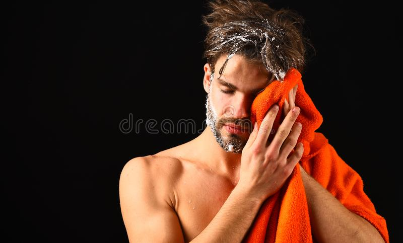 Macho attractive nude guy black background. Man bearded tousled hair covered with foam or soap suds. Wash off foam with. Water carefully. Man with orange towel stock image