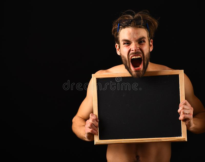 Macho attractive nude guy hold blackboard. Man with beard and tousled hair black background. Man muscular torso. Hold blackboard in front of his naked torso stock photography