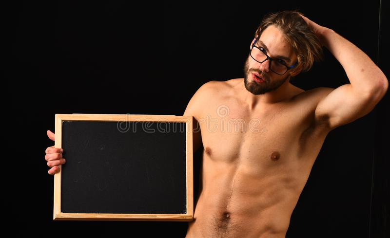 Macho attractive nude guy hold blackboard. Man smart and with beard and tousled hair wears eyeglasses. Man. Muscular torso hold blackboard near his naked torso royalty free stock images