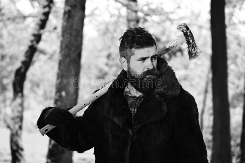 Macho with beard and mustache holds yellow ax. Guy near trees covered by snow on background, defocused. Brutal woodsman concept. lumberjack concept. lumberjack stock image