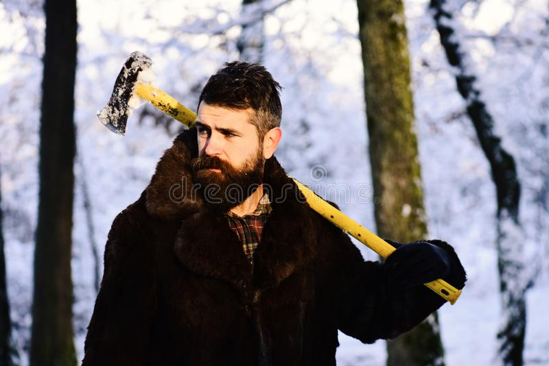 Macho with beard and mustache holds yellow ax. Guy near trees covered by snow on background, deed. Brutal woodsman concept. lumberjack concept. lumberjack man stock images