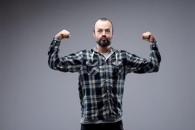 Macho bearded man flexing his arms royalty free stock photos