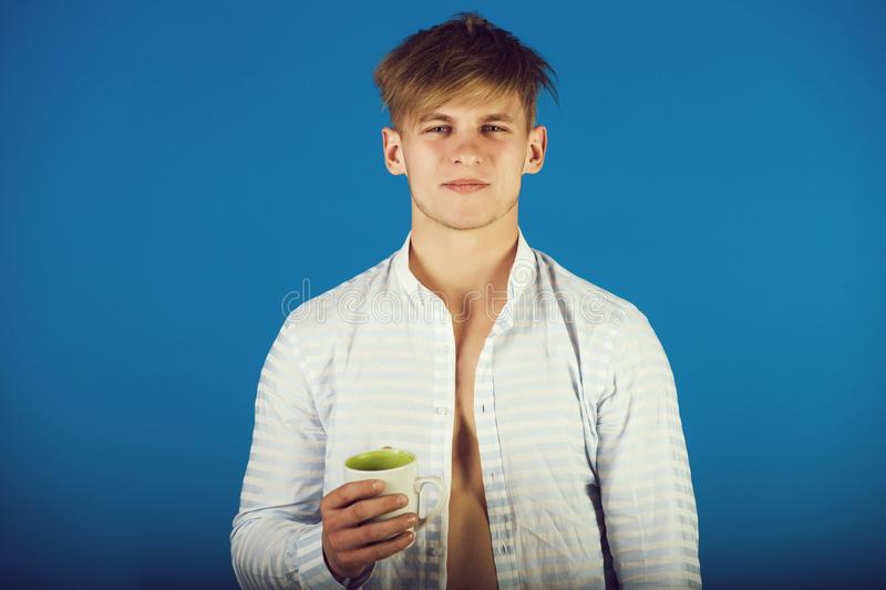 Macho with blond hair holding cup in open shirt stock images