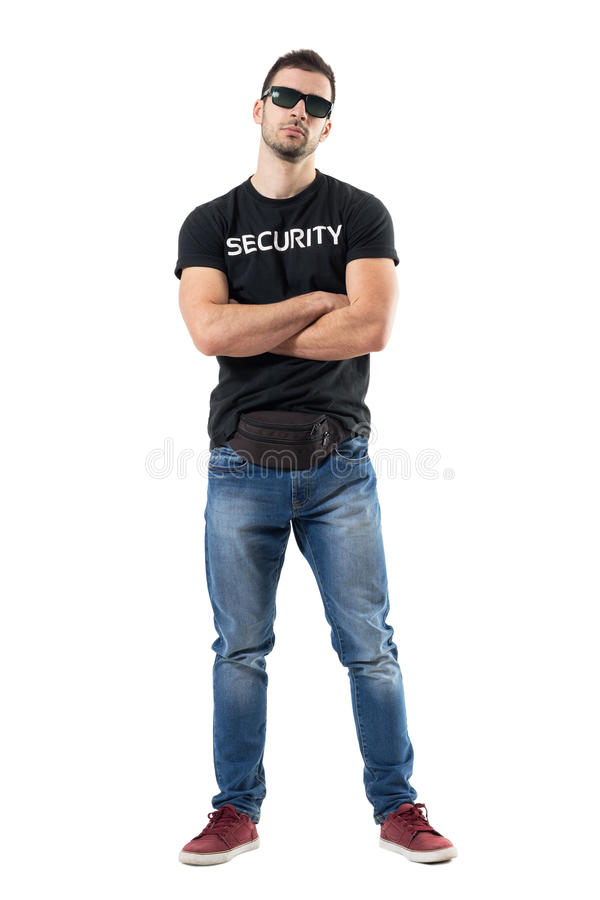 Macho bouncer or undercover cop in plain clothes looking at camera with crossed arms stock image