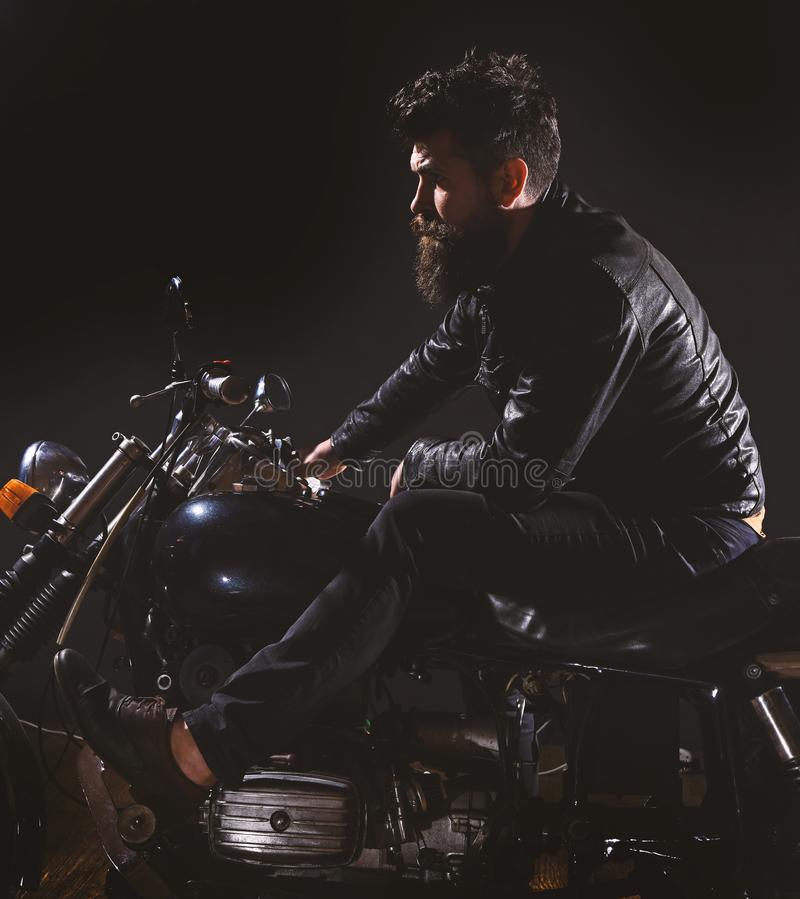 Macho, brutal biker in leather jacket riding motorcycle at night time, copy space. Bikers leisure concept. Man with. Beard, biker in leather jacket sitting on royalty free stock images