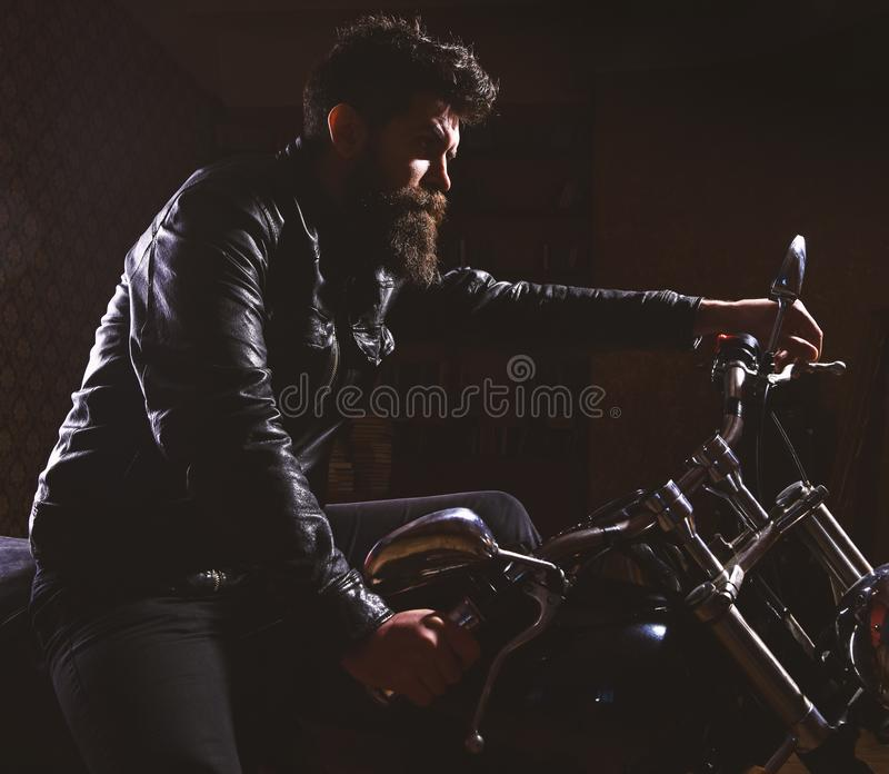 Macho, brutal biker in leather jacket riding motorcycle at night time, copy space. Man with beard, biker in leather. Jacket sitting on motor bike in darkness stock image