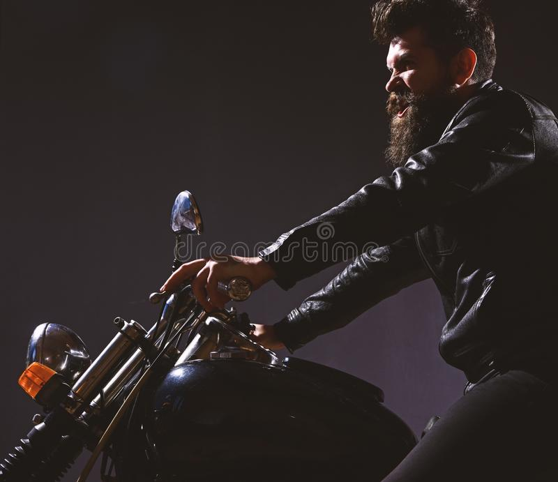 Macho, brutal biker in leather jacket riding motorcycle at night time, copy space. Masculinity concept. Man with beard. Biker in leather jacket sitting on stock image