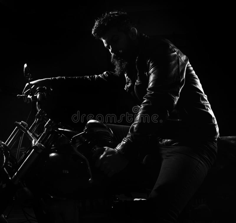 Macho, brutal biker in leather jacket riding motorcycle at night time, copy space. Night racer concept. Man with beard. Biker in leather jacket sitting on royalty free stock image