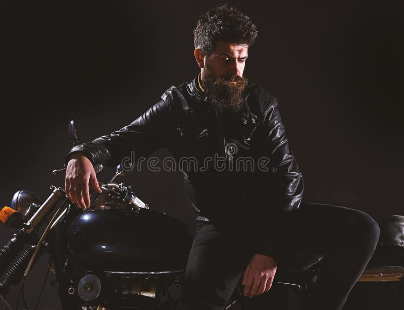 Macho, brutal biker in leather jacket stand near motorcycle at night time. Brutality and masculine concept. Man with. Beard, biker in leather jacket lean on stock photos