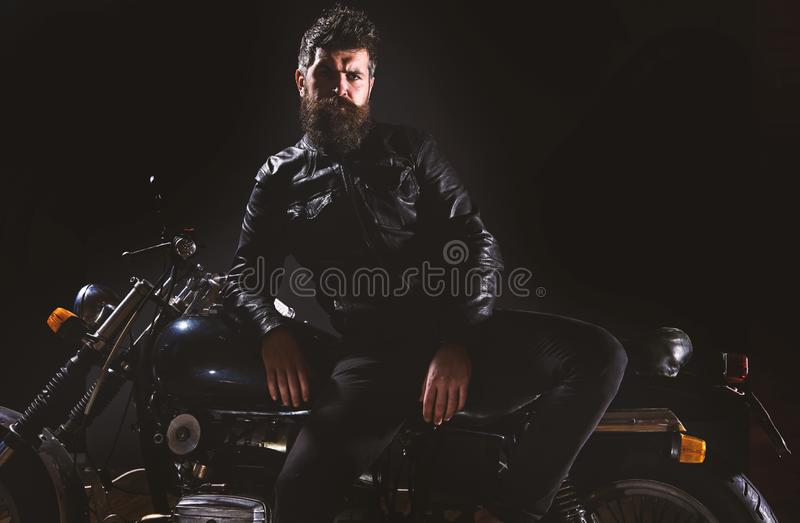 Macho, brutal biker in leather jacket stand near motorcycle at night time, copy space. Biker culture concept. Man with. Beard, biker in leather jacket lean on royalty free stock images