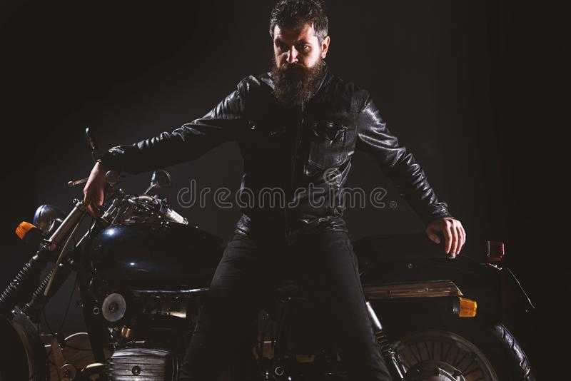 Macho, brutal biker in leather jacket stand near motorcycle at night time, copy space. Man with beard, biker in leather. Jacket lean on motor bike in darkness royalty free stock image