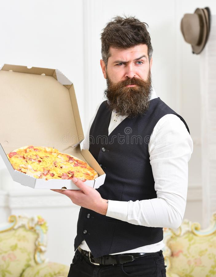 Macho in classic clothes hungry, on suspicious face, going to eat pizza, luxury interior background. Man with beard and stock images